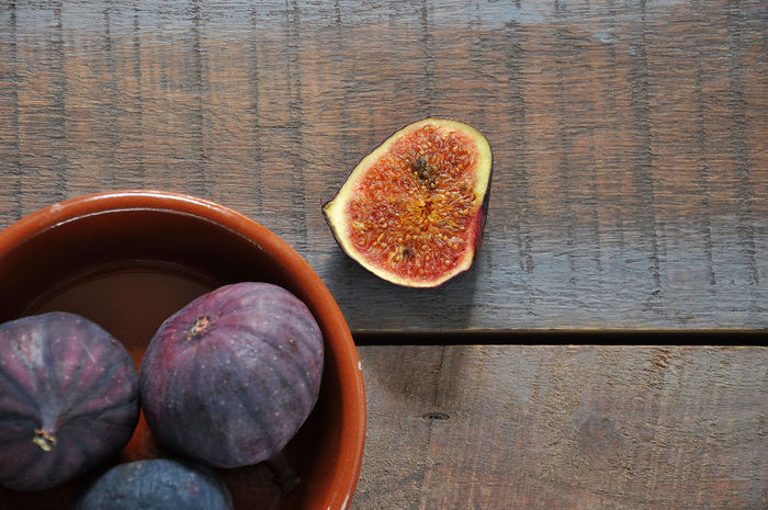 Directly Above Shot Of Figs On Wooden Table Bowl Close-up Color Image Cross Section Day Directly Above Fig Food Food And Drink Freshness Fruit Halved Healthy Eating Horizontal Indoors  Juicy No People Photography Raw Food Ready-to-eat Ripe Seed Still Life Table Tropical Fruit