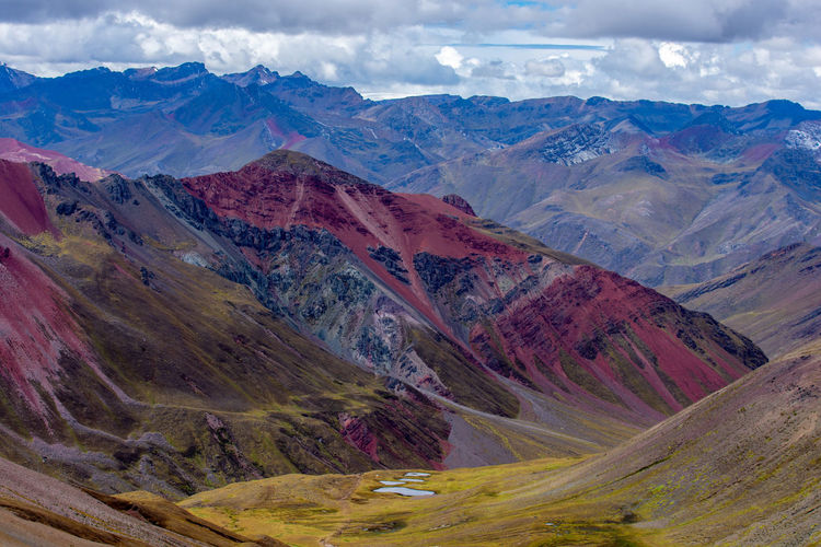Scenic view of red mountains against cloudy sky