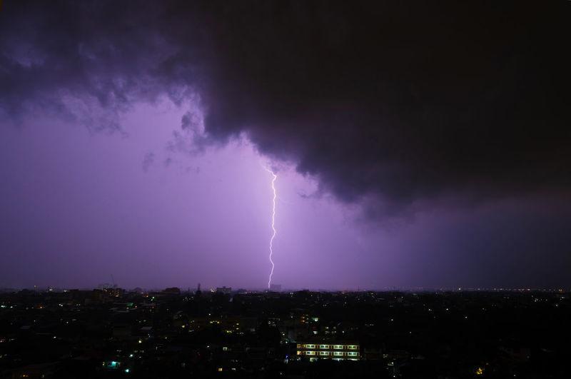 Lightning over illuminated cityscape against dramatic sky