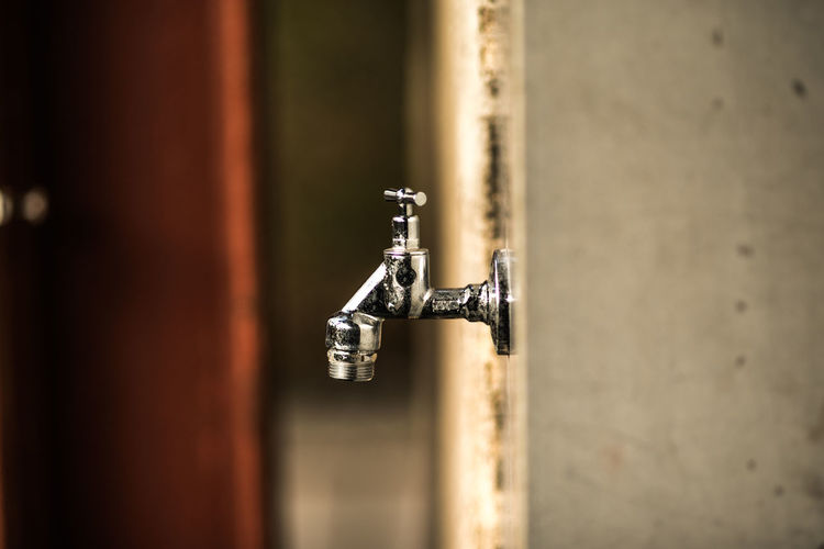 Close-up of faucet against white wall