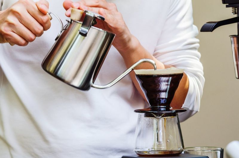 Midsection of man pouring coffee cup.