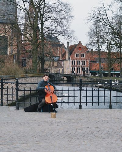 Portrait of young man playing cello on bridge in city