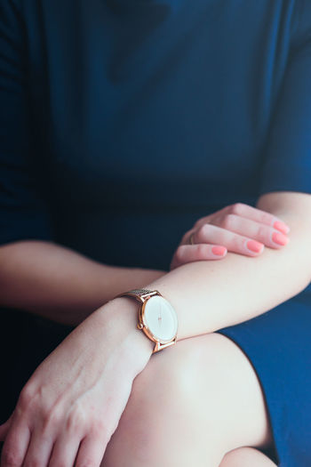Midsection of woman in dress wearing wristwatch