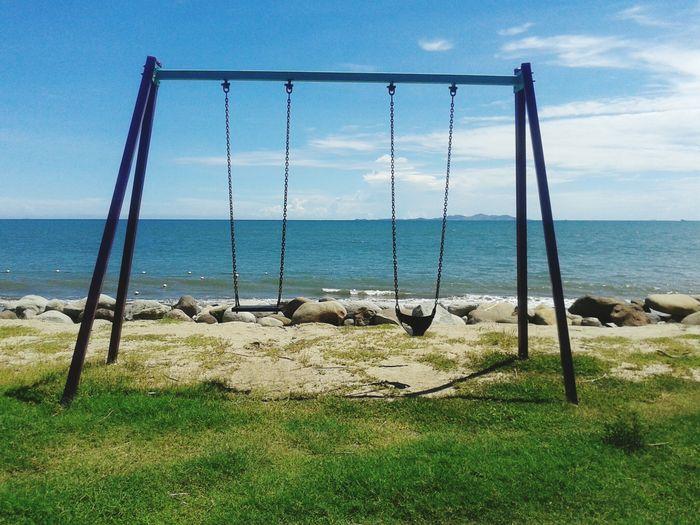 Empty Swings On Field By Sea Against Sky