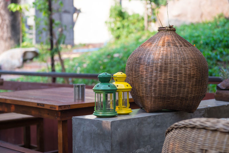 Vintage lanterns by wicker container on retaining wall in yard