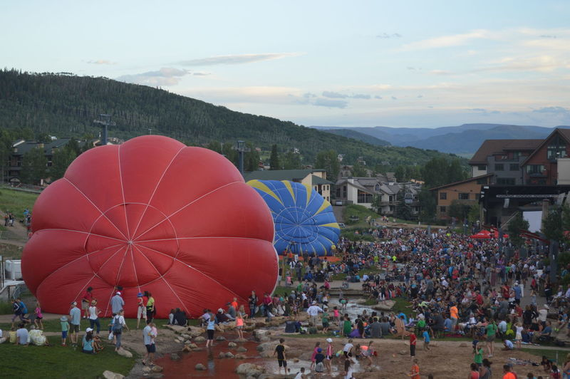 Crowd By Hot Air Balloon On Field In Town
