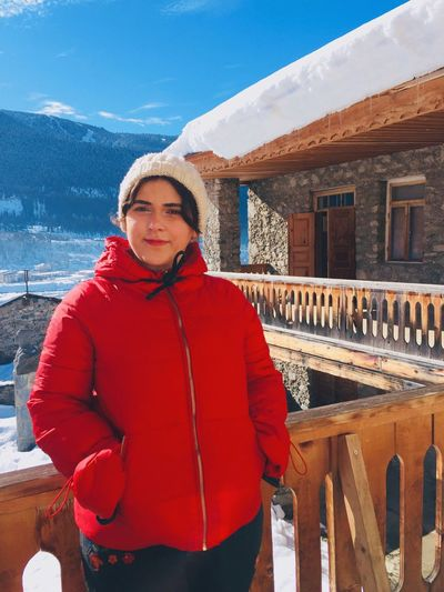 Portrait Of Smiling Young Woman Standing In Balcony During Winter