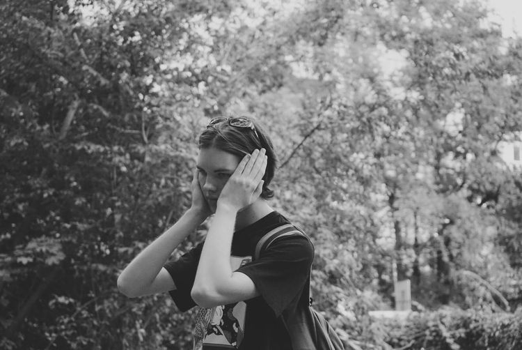 Teenage boy covering ears while standing against trees