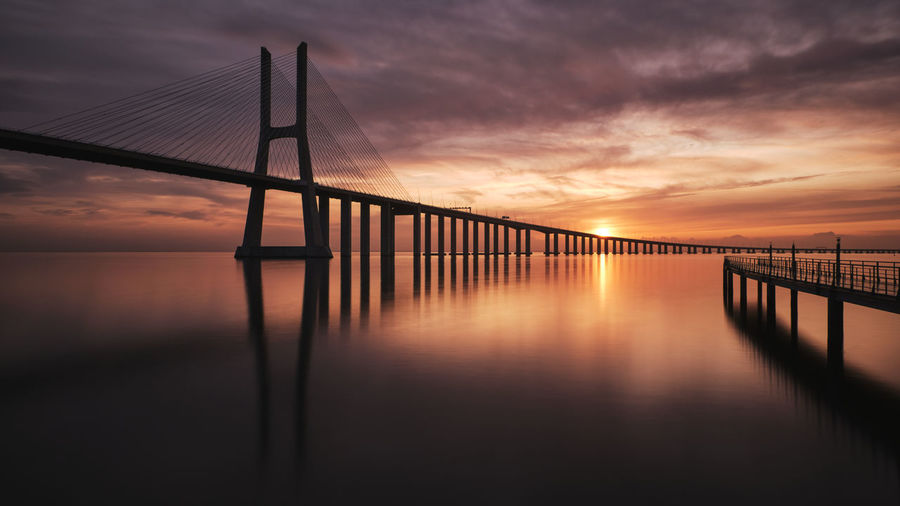 Silhouette bridge over sea against sky during sunset