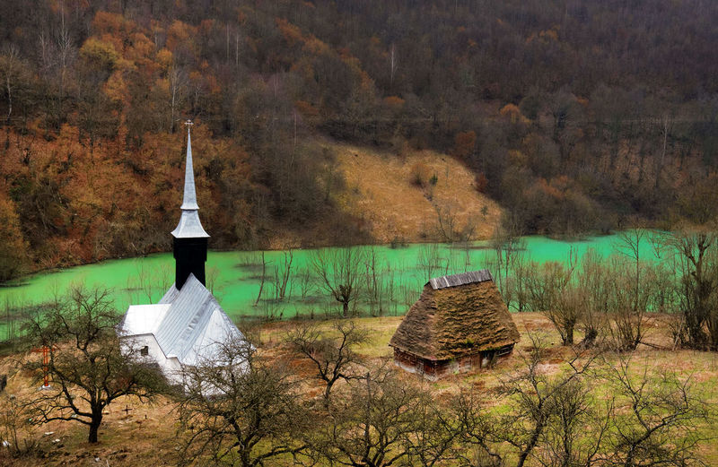 High angle view of church on field by polluted lake against forest