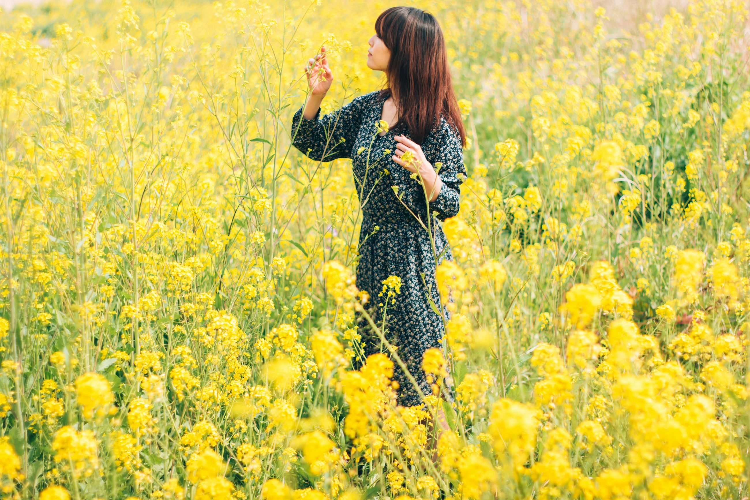 beauty, flower, beauty in nature, nature, happiness, yellow, females, beautiful people, carefree, harmony, rear view, field, day dreaming, young adult, idyllic, freedom, rural scene, tranquil scene, springtime, smiling, summer, outdoors, women, cheerful, beautiful woman, one person, adult, agriculture, people, freshness, human body part, day