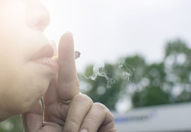 Asian old woman smoking a cigarette with bokeh tree background Asian  Smoking Tree Woman Bad Habit Body Part Bokeh Cigarette  Day Finger Holding Human Body Part Human Face Human Hand Lifestyles One Person RISK Smell Smoking - Activity Smoking Issues Unhealthy