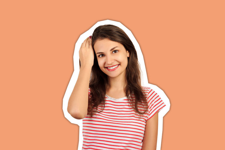 Portrait of a smiling young woman against orange background