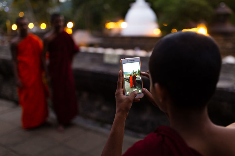 Close-up of person photographing with mobile phone at night