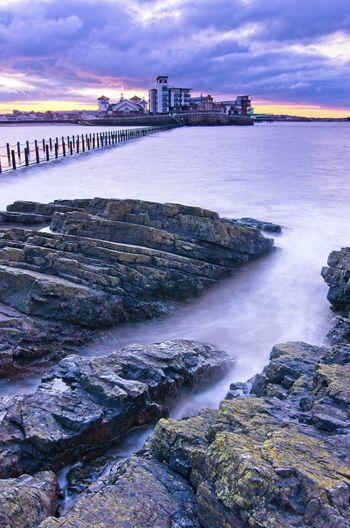 A long exposure of knightstone island, the causeway and marine lake at sunset with a high tide.
