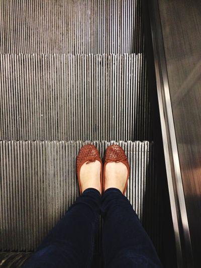 Woman standing on a escalator