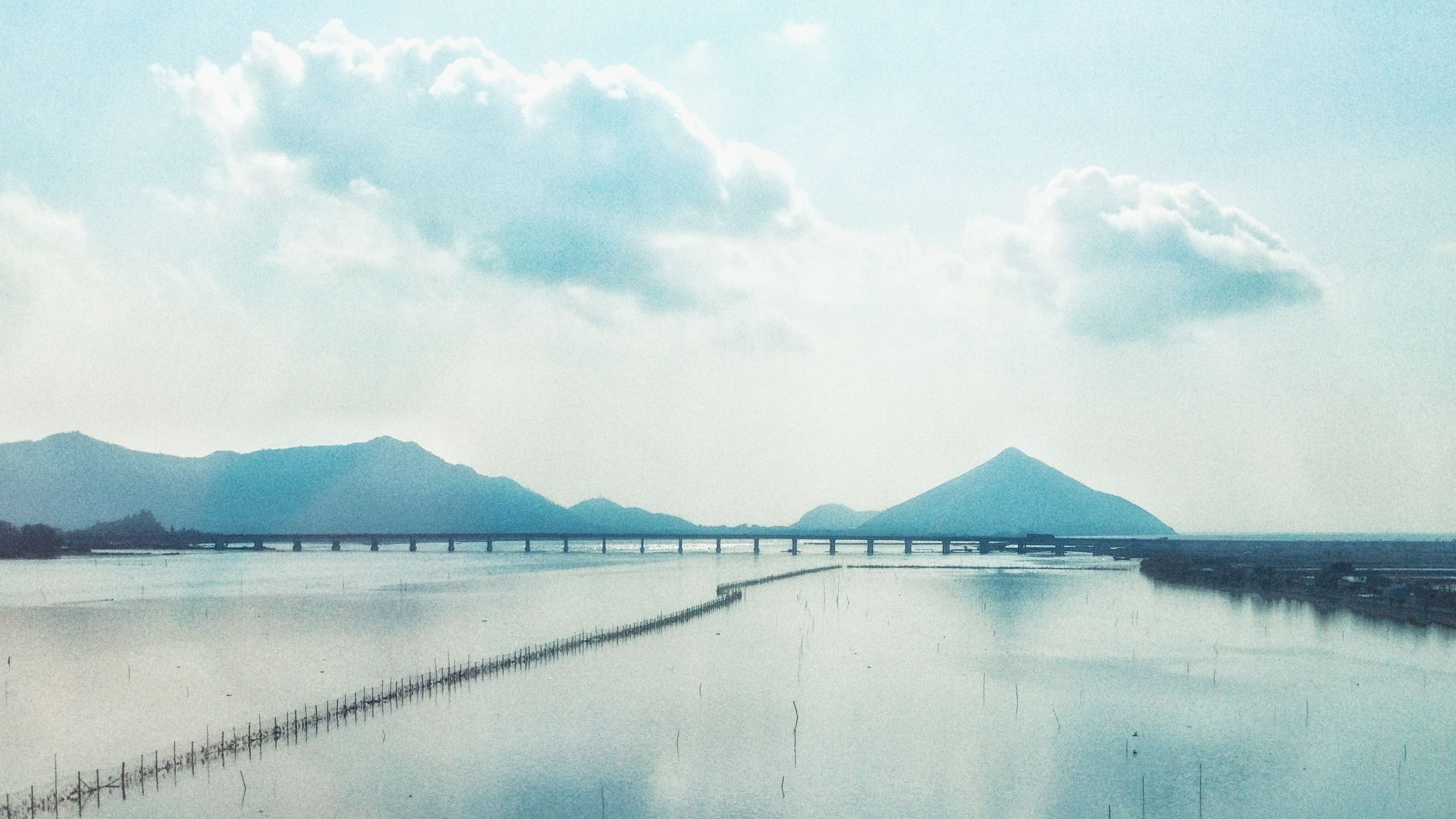 water, sky, sea, tranquil scene, mountain, tranquility, cloud - sky, scenics, beach, beauty in nature, cloud, built structure, nature, pier, day, waterfront, lake, architecture, shore, calm