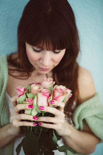 Close-up of woman smelling roses