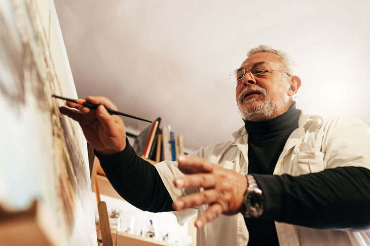 Low angle view of senior man painting
