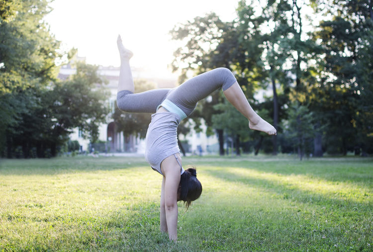 Relaxing Balance Day Exercising Field Flexibility Full Length Grass Handstand  Healthy Lifestyle Legs Apart Leisure Activity Lifestyles Nature Outdoors People Sports Clothing Tree Women Yoga Young Women