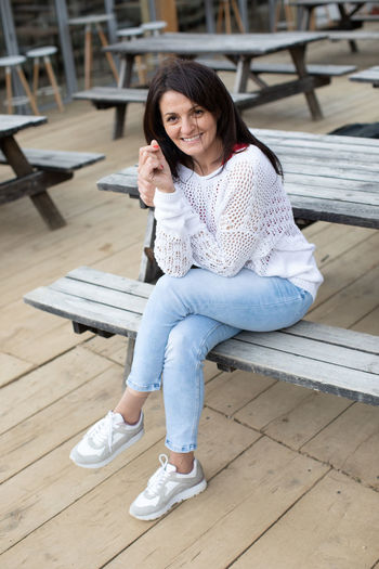 Full length of smiling woman sitting on wooden bench