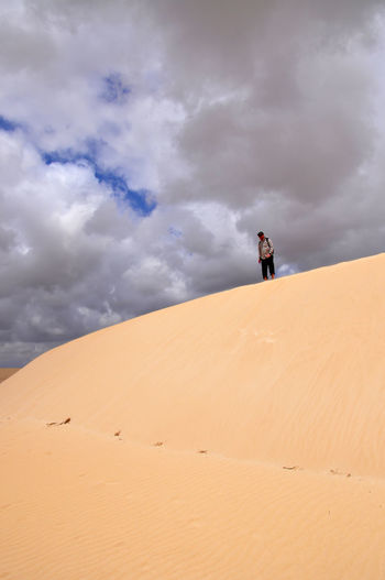 Low Angle View Of Man Standing At Desert Against Cloudy Sky