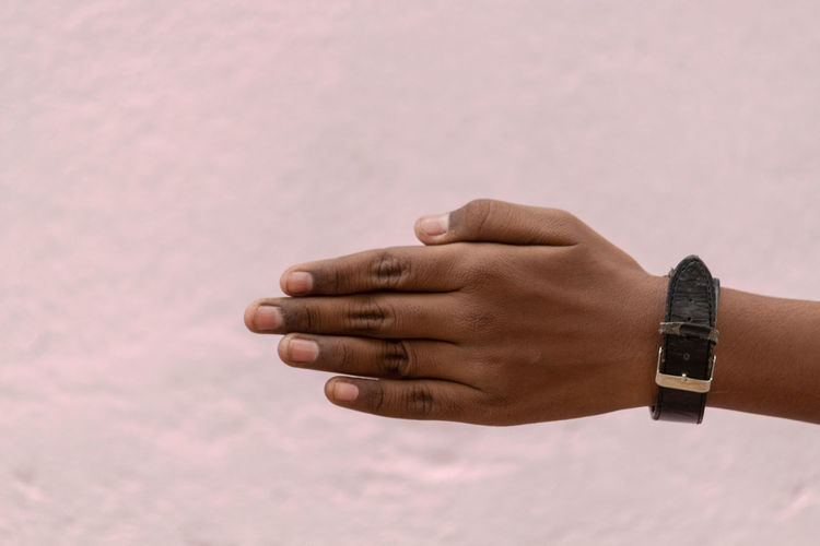 Close-up of hand against pink wall