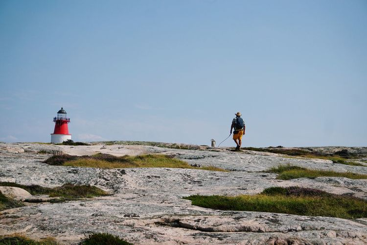 Rear View Of Man With Dog Walking Towards Lighthouse On Mountain