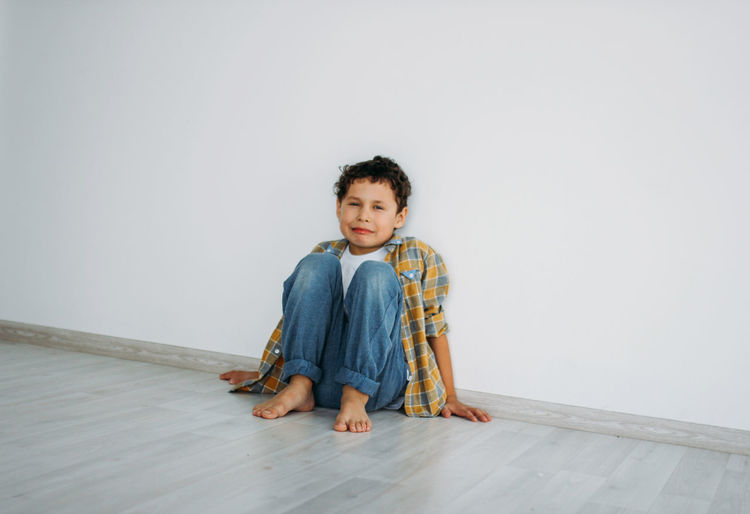 Portrait of crying boy sitting on floor against wall at home