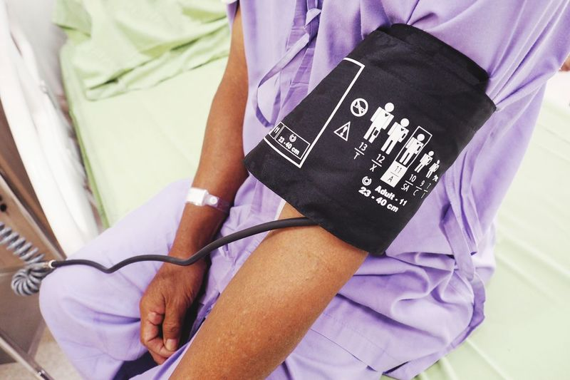 Midsection of male patient with blood pressure gauge in hospital
