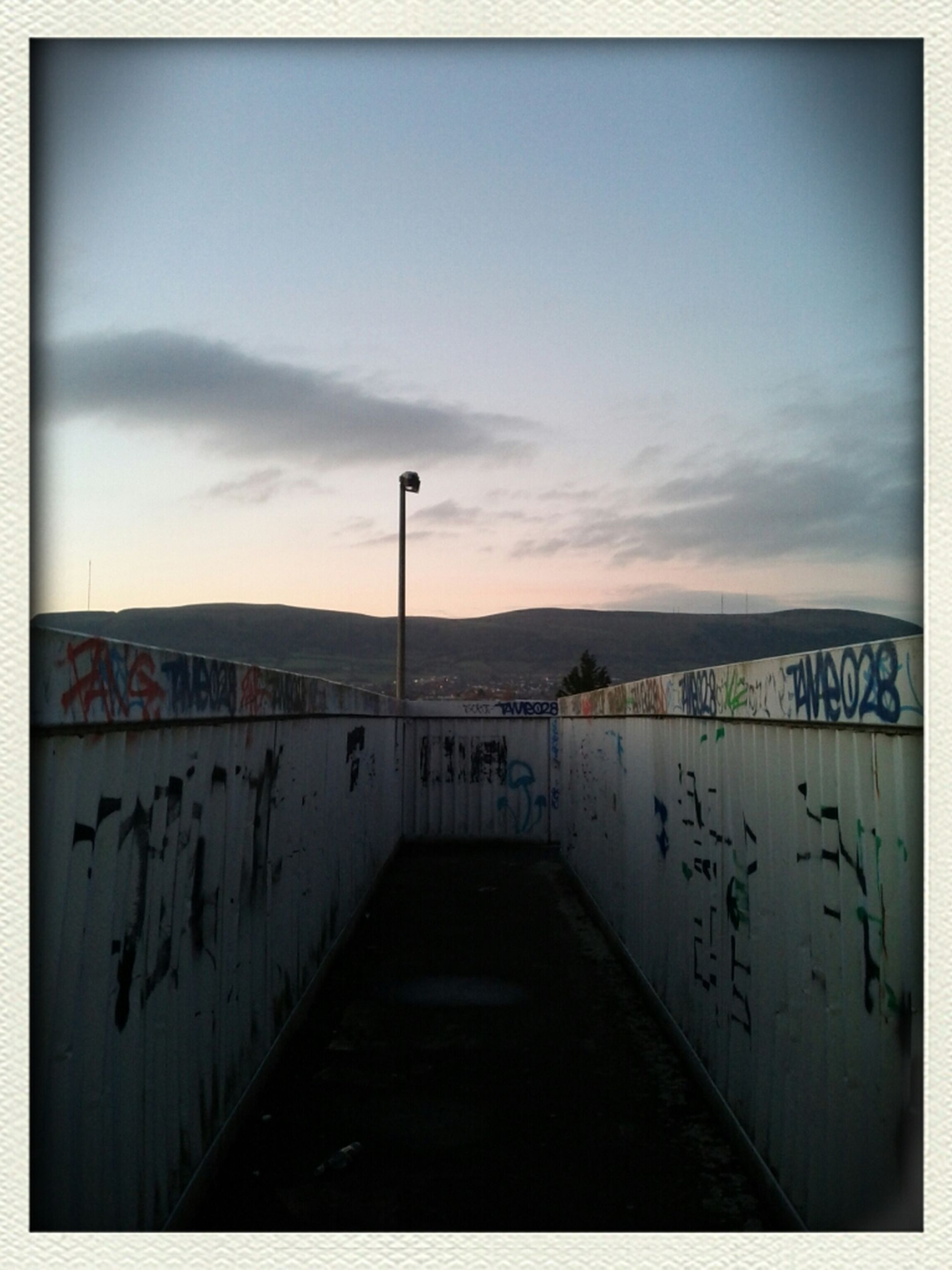 sky, built structure, architecture, graffiti, text, the way forward, western script, building exterior, wall - building feature, communication, cloud - sky, auto post production filter, cloud, wall, outdoors, day, no people, empty, sign, railing