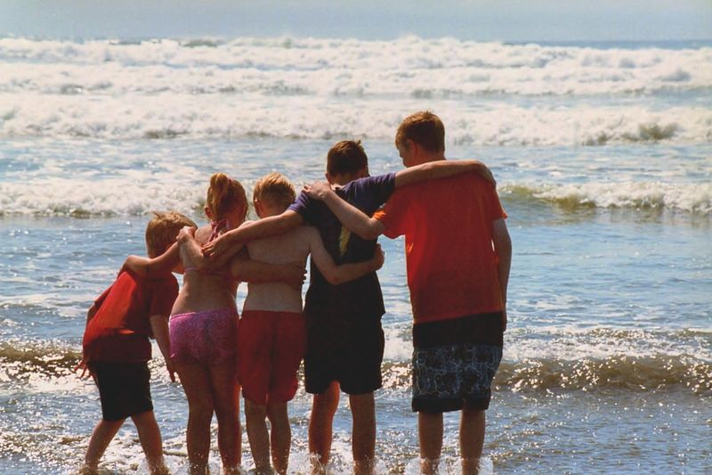 Rear View Of Friends Standing On Shore At Beach