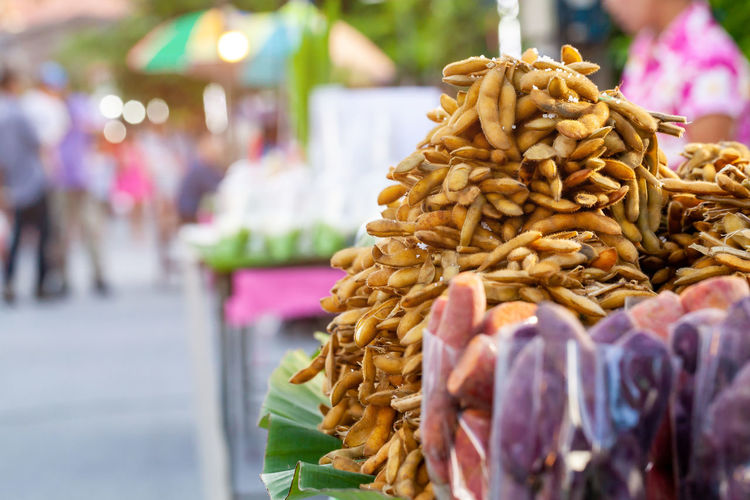 Stacked dry tamarinds for sale at market stall