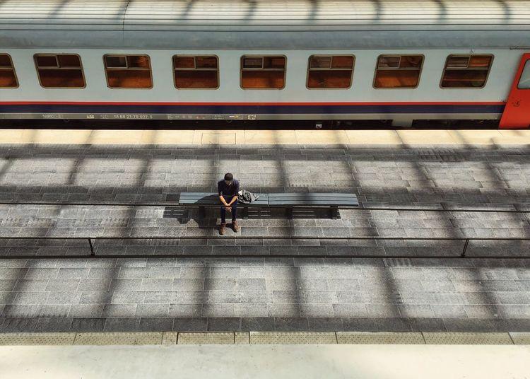 High angle view of man sitting at railroad station platform