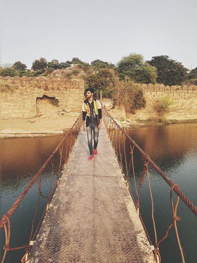 People standing on bridge against clear sky