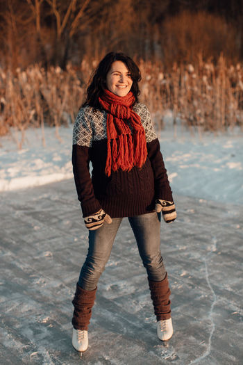 Happy woman enjoying ice skating on a frozen lake December Frozen Ice Natural Pond Winter Woman Cold Female Gloves Hobby Ice Skater Ice Skating Knitwear Lake Leisure Activity Outdoor Rink Season  Skates Skating Snow Snowy Sport Sunset