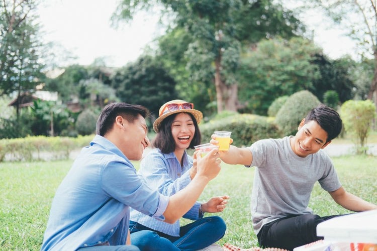 Friends Toasting Drinks While Sitting At Park