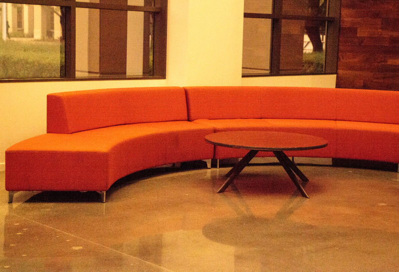 Modern curved orange couch in front of large windows with a round coffee table. Coffee Table Couch Architecture Art Deco Art Deco Architecture Art Deco Design Chair Close-up Day Furniture Indoors  No People Orange Couch Post Modern Seat Sectionals Sofa Table Vintage
