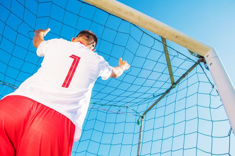Goalkeeper with Number One on the Tshirt in the Goal. European Football Theme. Soccer Playing. Football Arms Raised Gamer Goal Goalkeeper Human Arm Low Angle View Match Outdoors Player Soccer Sport Standing Tournament Young Adult