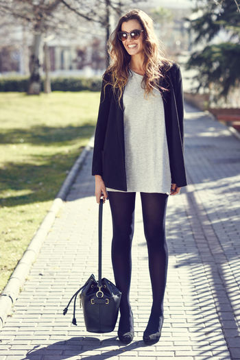 Happy Young Woman Holding Handbag While Standing On Footpath