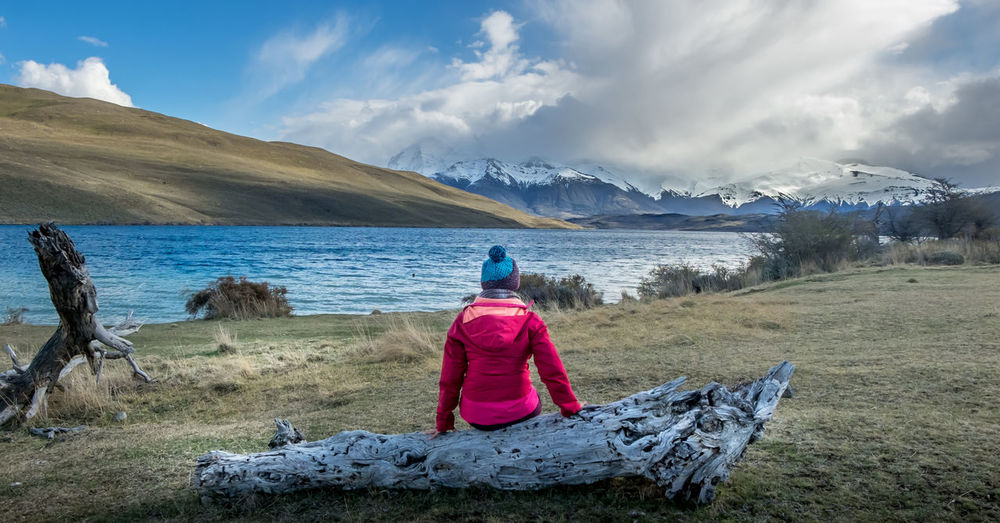 A woman sitting on a wood overlooking Laguna Azul (Blue Lake) in Torres del Paine, Chile Beauty In Nature Cloud - Sky Cold Temperature Day Grass Horizon Over Water Lake View Landscape Mountain Nature One Person Outdoors Patagonia Real People Rear View Scenics Sitting Sky Snowcapped Mountain Torres Del Paine Tranquil Scene Tranquility Vacations Winter Women