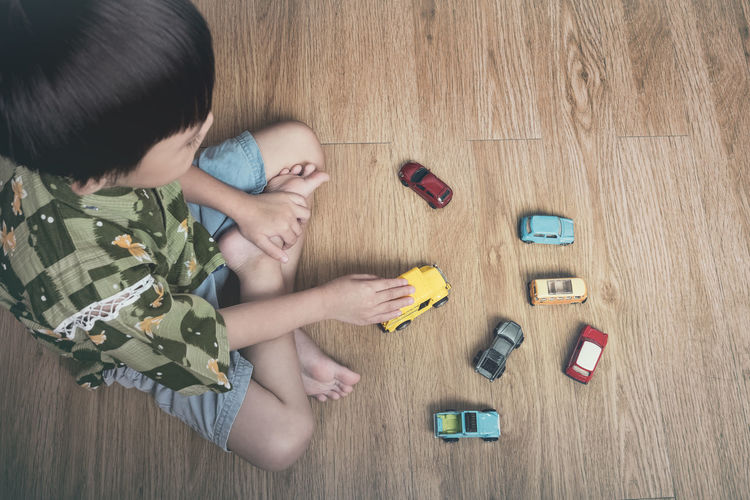 High angle view of boy playing with toy cars on hardwood floor