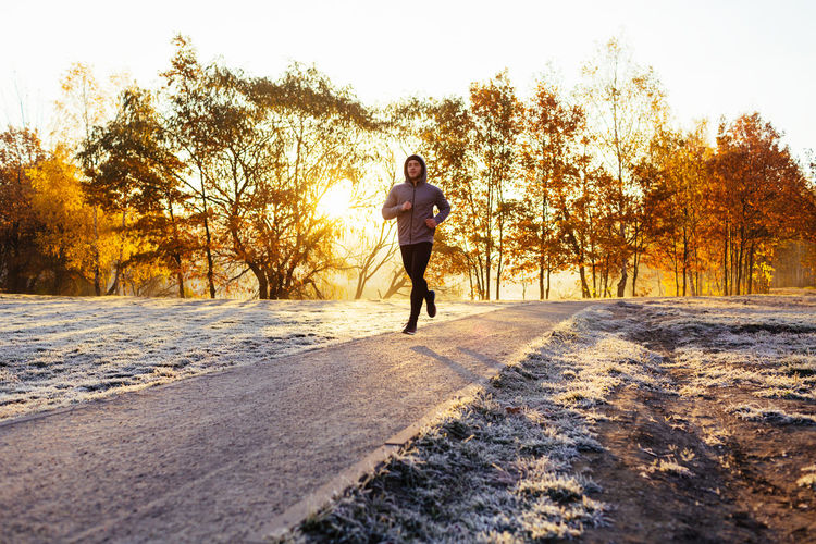 Young man running during cold autumn morning Effort Morning Run Running Sunny Adult Athlete, Autumn Cold Temperature Day Exercising Full Length Healthy Lifestyle Jogging Lifestyles Men One Person Outdoors Park People Road Run-down Running Sport Sports Clothing