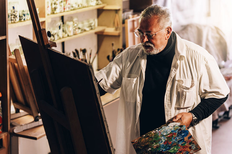 Senior man painting on easel