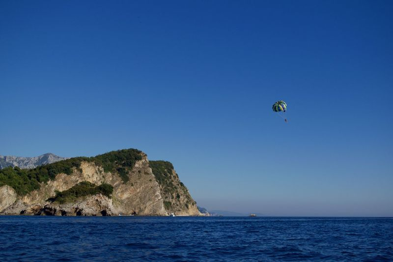 Person parasailing over sea against clear blue sky