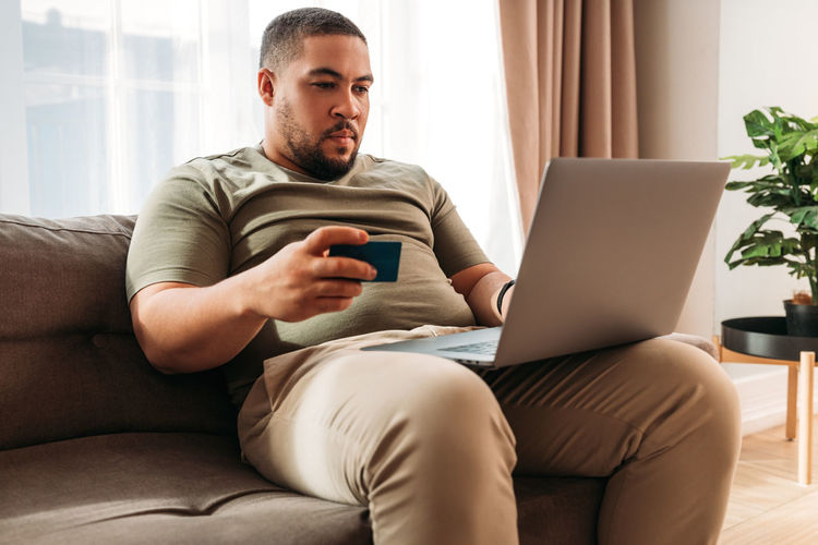 Young man using mobile phone while sitting on sofa at home