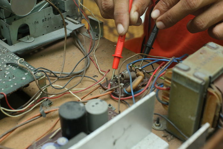 Cropped Hands Of Male Technician Repairing Radio