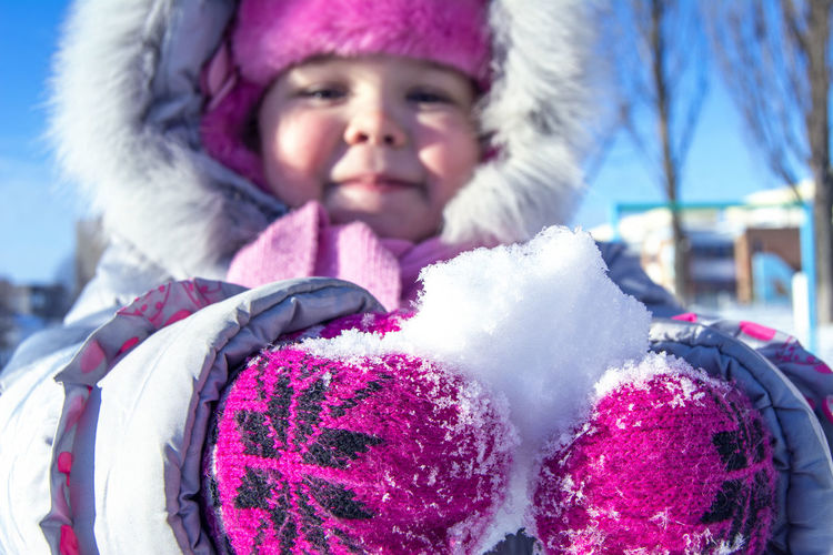 Close-Up Of Child Holding Snow