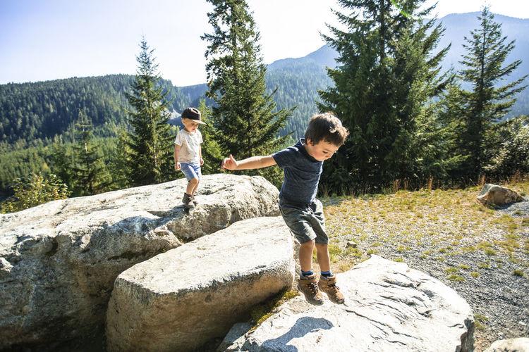 Full length of friends on rock against mountain