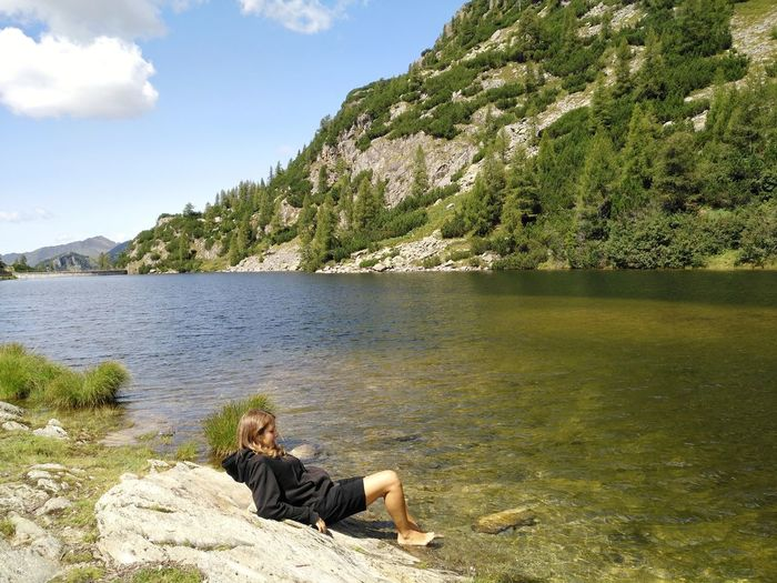 Woman sitting on rock by lake against sky